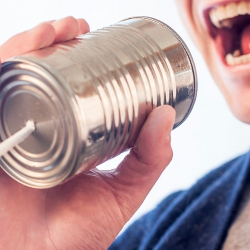 A man speaking into a tin can. It's just like using video marketing to achieve your goals.