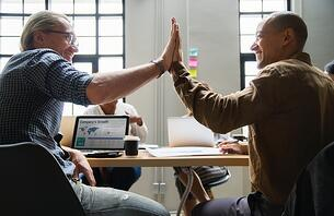 Two men high fiving because they found great explainer video companies