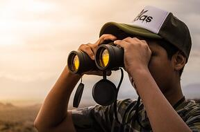 a man using binoculars to help him find the best explainer video company