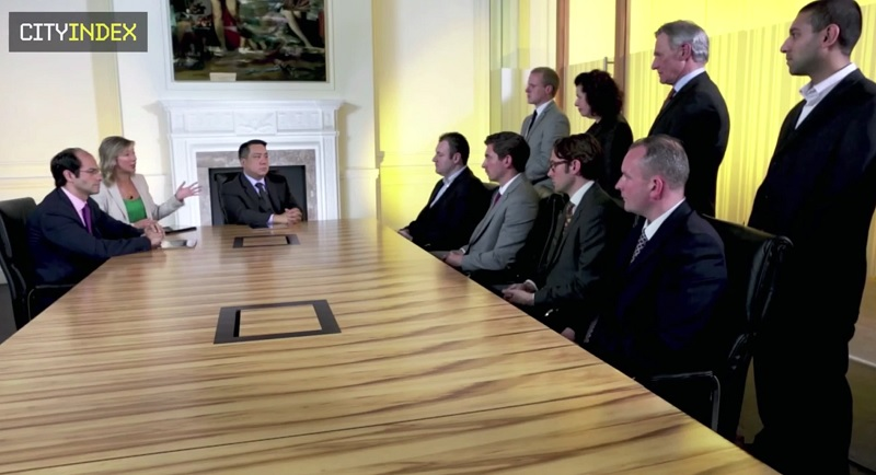 A group of wannabe traders sit around a table with a presenter and some judges.