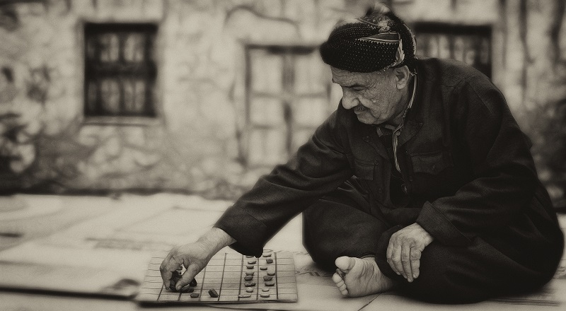 An old man playing some sort of board game. He wishes he was doing something cooler.