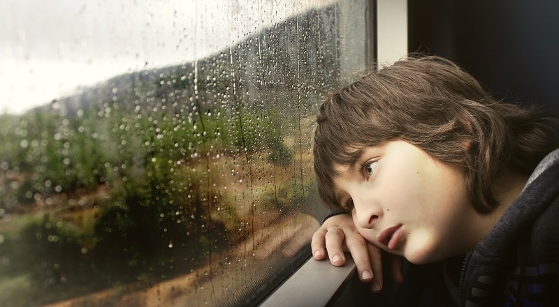 A sad kid looking out of a window tracked with rain. Because his video marketing isn't going well.