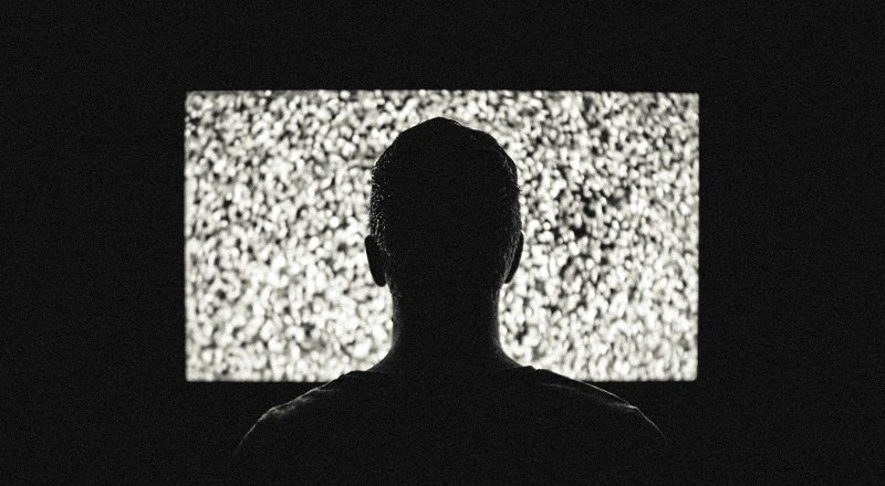 A man sitting in the dark in front of a TV screen full of static.